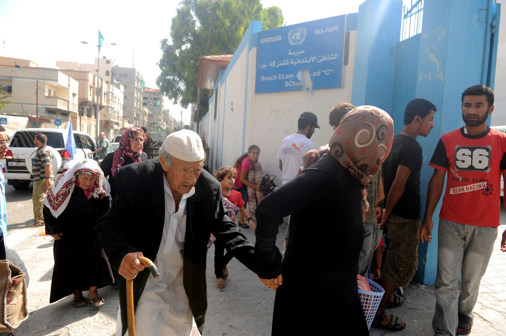 Palestinian families travel to an UNRWA school to seek shelter after evacuating their homes near the border in Gaza City during the conflict in 2014. UN Photo/Shareef Sarhan