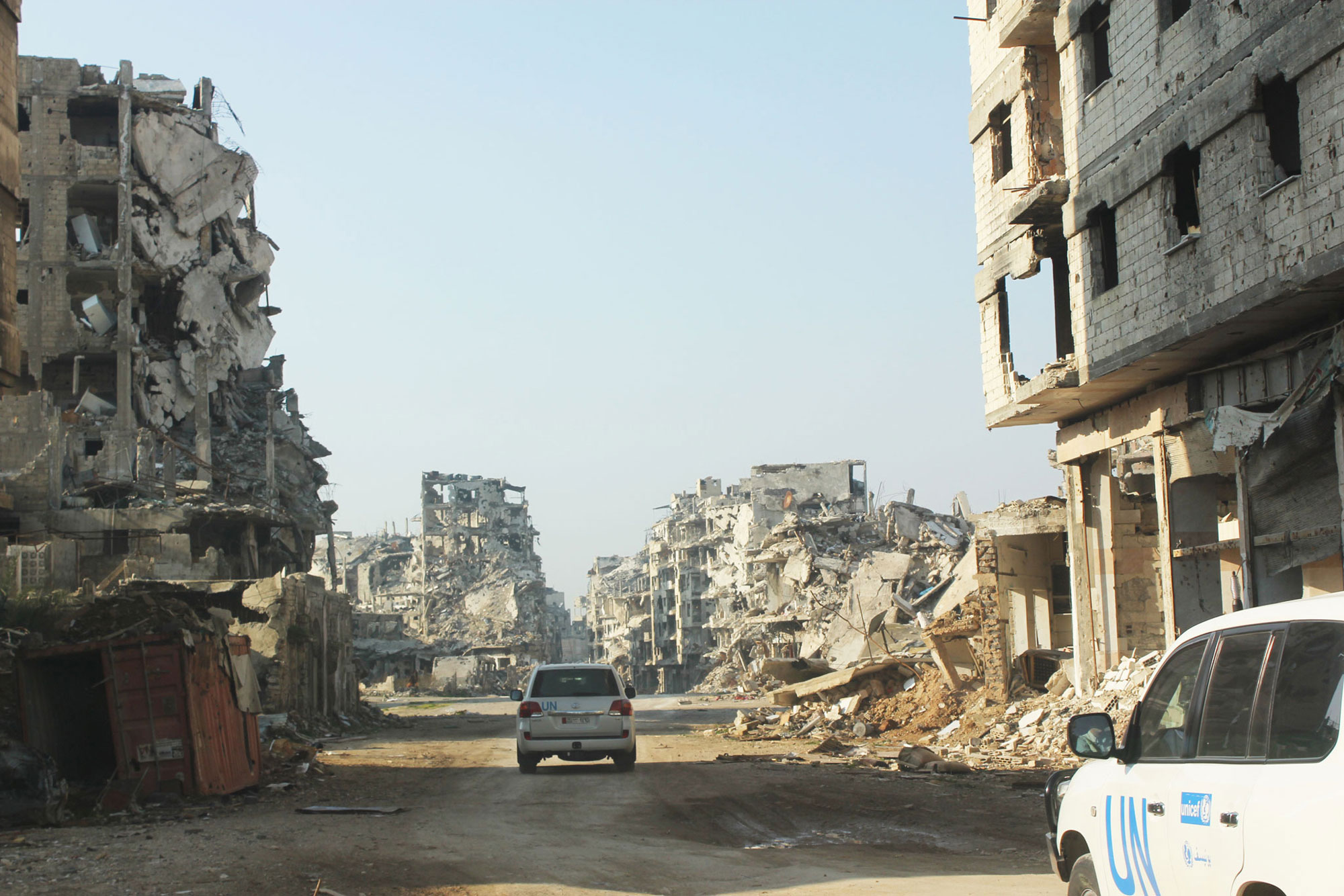 In the Old City of Homs, Syria, UN vehicles travel a dusty road lined with rubble and remnants of destroyed buildings. UNICEF/UNI178367/Tiku