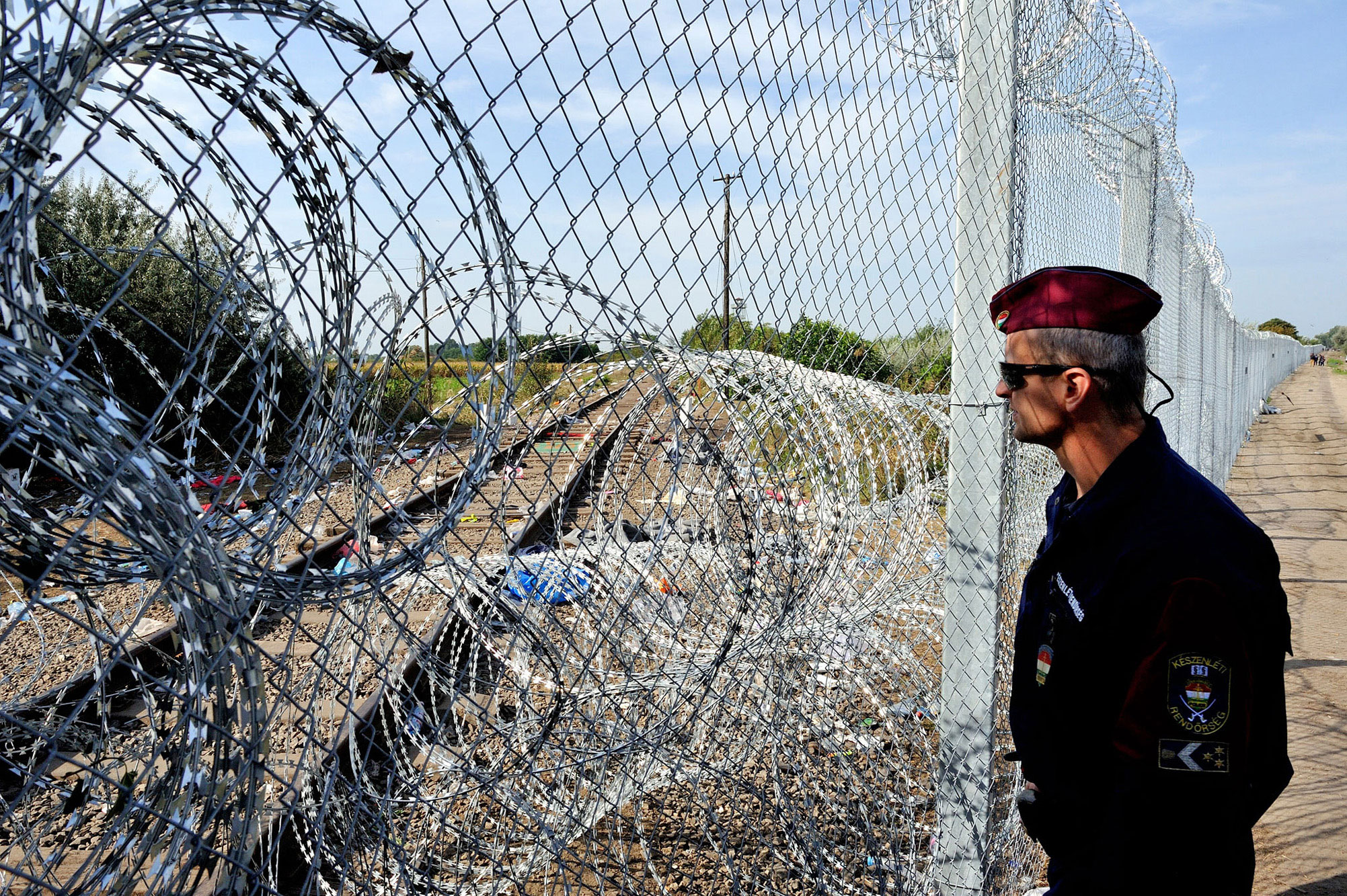 In Hungary, police stand guard at a border fence topped with razor wire aimed at stopping the flow of refugees and locking them out of the European Union. UNHCR/Mark Henley