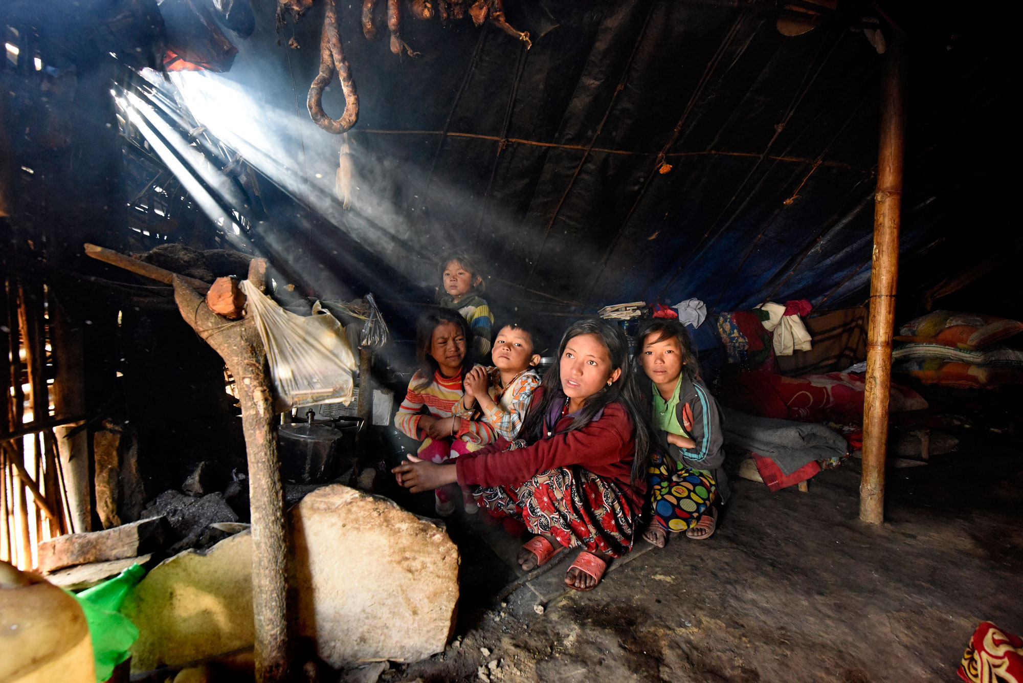 Children warm themselves by a fire inside their temporary shelter in Rasuwa, one of the areas worst affected by the earthquakes that struck Nepal earlier in the year. Their tent is not winter-resistant and often gets cold even in the pre-winter season, and the family does not have warm clothing. UNICEF/UN04381/Karki