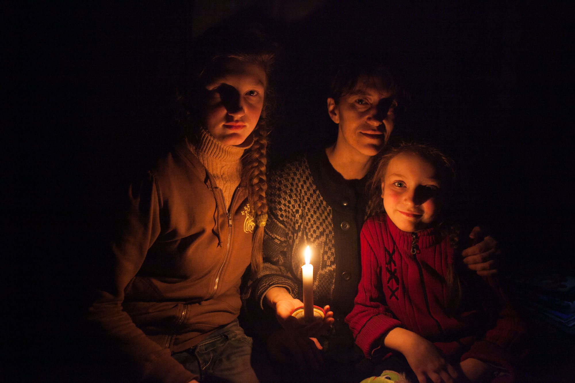 In Donetsk, eastern Ukraine, a woman and her daughters sit in a candlelit bomb shelter on the outskirts of the city of Debaltsevo. UNICEF/UNI179968/Filippov