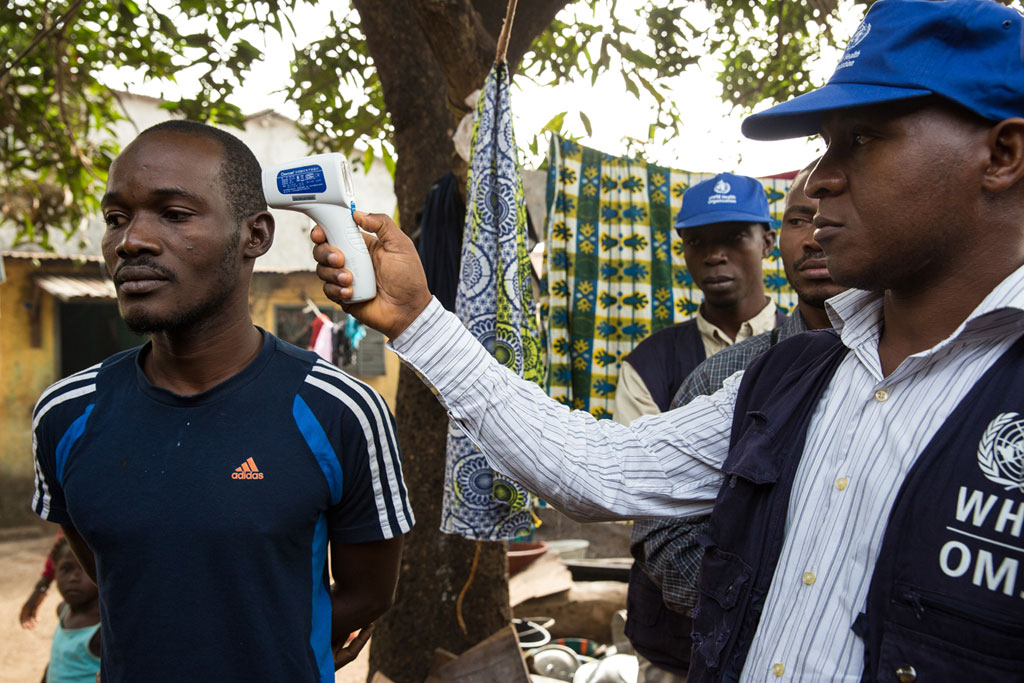 A World Health Organization (WHO) doctor checks a man's temperature in Conakry, Guinea, in January 2015. Efforts to halt the spread of Ebola including contact tracing, or finding persons who have been in close contact with persons infected with the disease and monitoring them to see if they have also become infected. UN Photo/Martine Perret