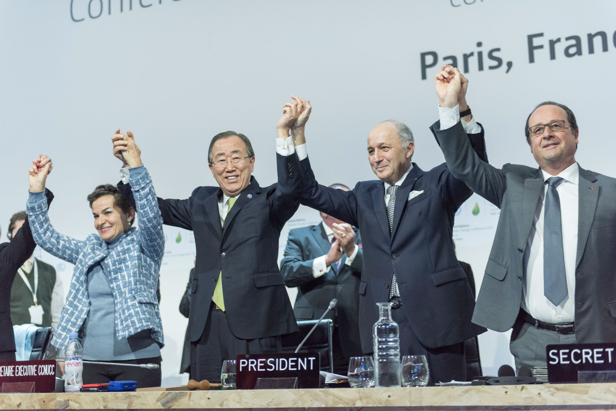 Secretary-General Ban Ki-moon (second left), UNFCCC's Christiana Figueres (left), French Foreign Minister Laurent Fabius and President of the UN Climate Change Conference in Paris (COP21), and President François Hollande of France (right), celebrate historic adoption of Paris Agreement. UN Photo/Mark Garten