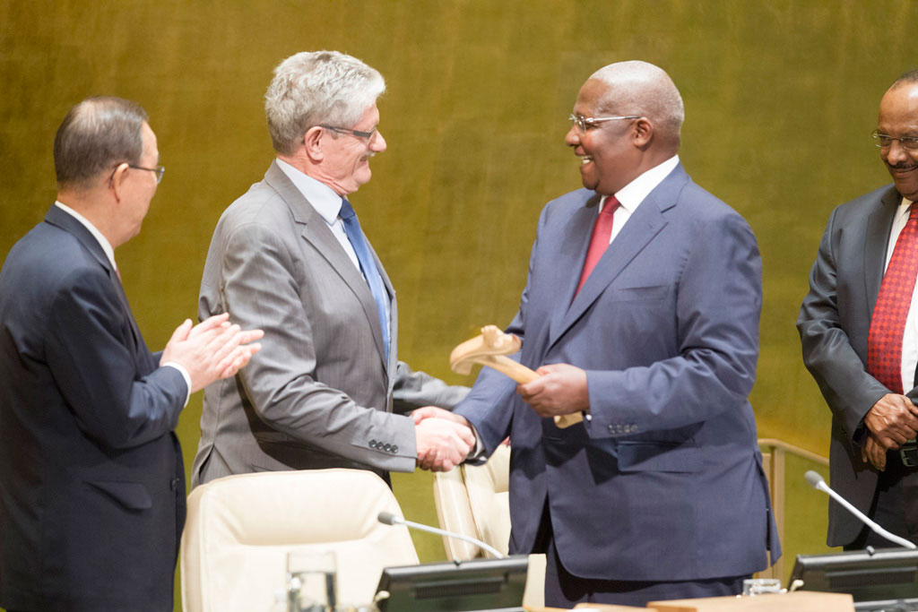 On the eve of the General Assembly's seventieth session, Sam Kutesa (Uganda), President of the sixty-ninth session, invites Mogens Lykketoft to the podium and hands over the gavel as Secretary-General Ban Ki-moon applauds (left). UN Photo/Rick Bajornas