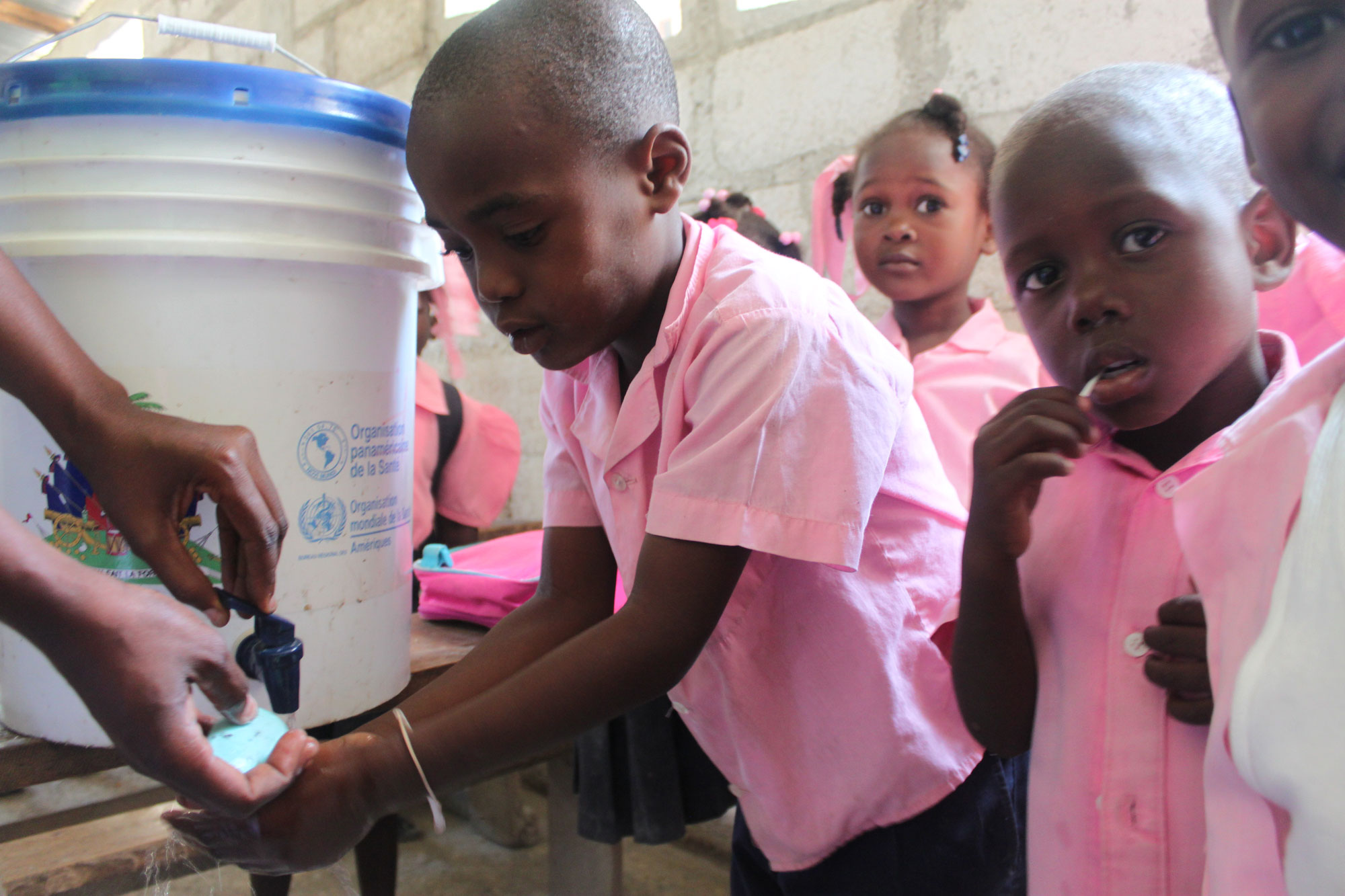 A group of Haitian children learn how to properly wash their hands in an effort to raise awareness about cholera prevention. UN Photo/ Logan Abassi