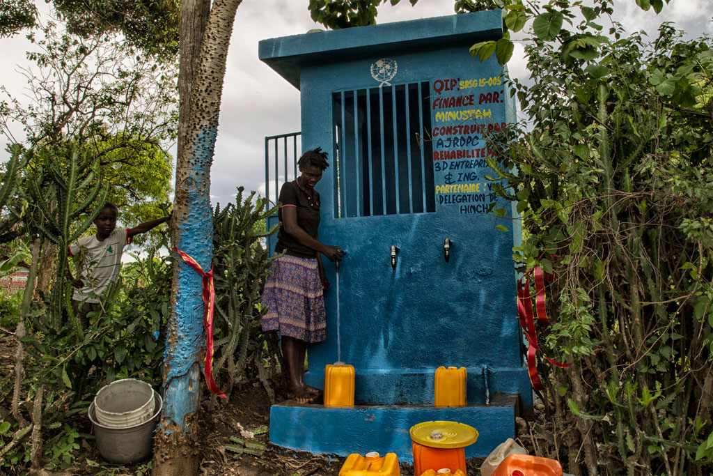 A woman along with her son, fills her containers at a water distribution point in Las Palmas, Haiti. MINUSTAH/Logan Abassi