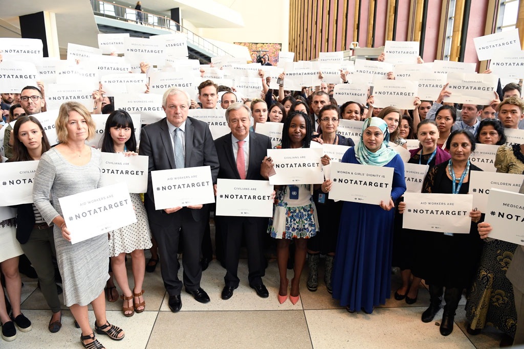 "Mr. O'Brien (front centre left) and Secretary-General António Guterres (front centre) pose for a group photo with participants at a special event under the theme, ""Staff Stand Together"", marking this year's World Humanitarian Day. UN Photo/Evan Schneider"