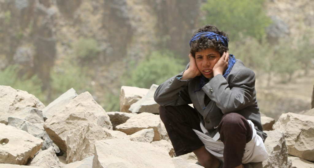 A boy sits amid rubble, all that remains of his home – which was destroyed in an air strike – in Okash Village, near Sana'a, the capital of Yemen.