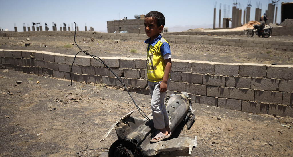 A boy stands atop a large piece of exploded artillery shell, which landed near his home in the village of Al Mahjar, a suburb of Sana'a.