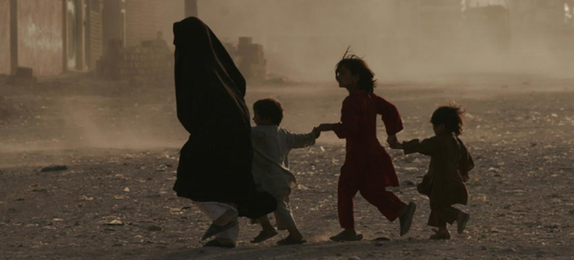 A family struggles through a dusty environment in Afghanistan. Photo