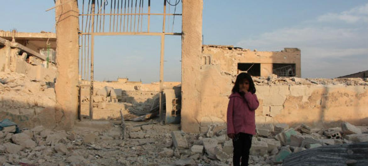 A seven-year-old child stands in front of her damaged school in Idleb, Syria. October 2016.