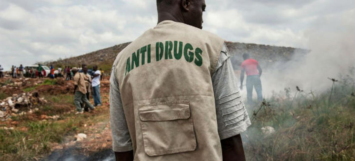 A staff member of the Liberia National Police Anti-Drug Squad reviews the municipal dump outside Monrovia, Liberia.