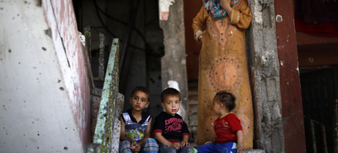 Toddlers sit on the top step and their grandmother stands on a landing, inside their partially destroyed home in the Shejaiya neighbourhood of Gaza City. UNICEF/UNI188296/El Baba