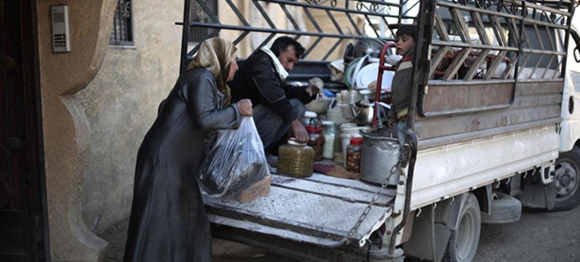 In December 2015, a mother loads preserved food supplies in a truck as the family prepares to move out of Nashabieh village to a neighbouring safer town within besieged East Ghouta, Syria. Almost 400,000 people are trapped in besieged locations.