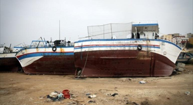 Abandoned migrant boats lie lifeless opposite the port of Lampedusa, Italy, an island which experiences frequent migration from nearby North Africa.