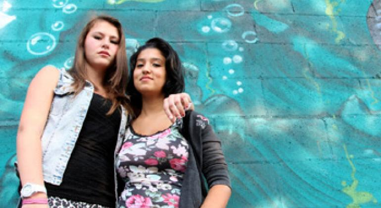 Daniela Cojocaru (left) and Chiara Dimastromatteo, both 16, stand next to a graffiti-covered wall in Turin, Italy. Daniela is originally from Moldova. Chiara does not attend school and does not have a job.
