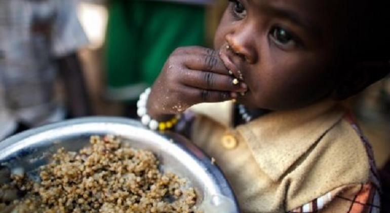 A child has a meal at a food distribution centre.