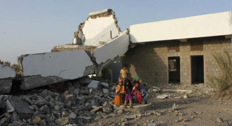Children sitting in front of a school that was badly damaged in the conflict in Yemen.