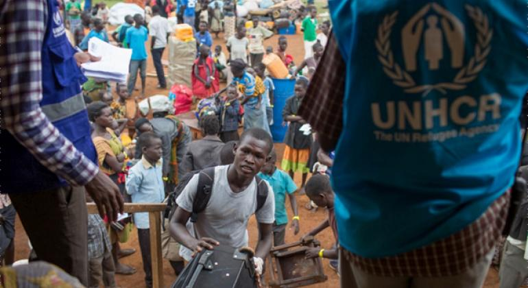 A recently arrived South Sudanese refugee loads his belongings into a UNHCR truck at the South Sudan border with Uganda.