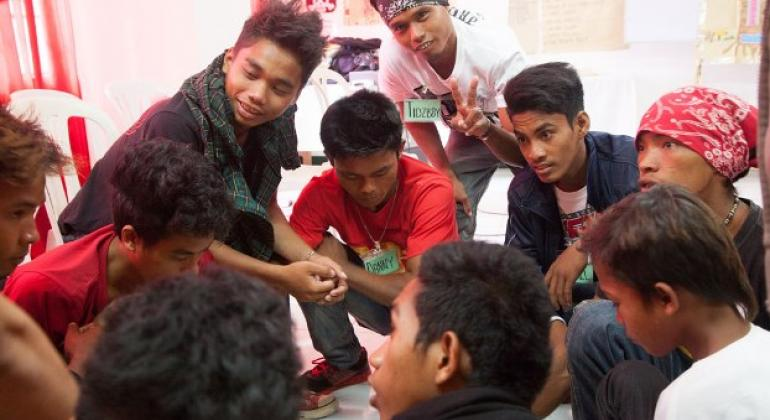 Youth volunteers and counsellors discussing protection against HIV through correct knowledge and skills, with a group of adolescent boys in Zamboanga City, Philippines.