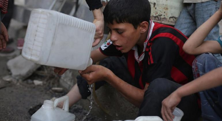 A boy drinks the remaining water in his jerrycan while waiting with other children in a queue for safe water in Rural Damascus, Syria.