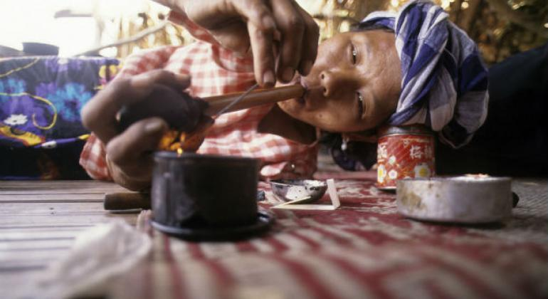 a woman from a hill tribe in Thailand smoking opium .