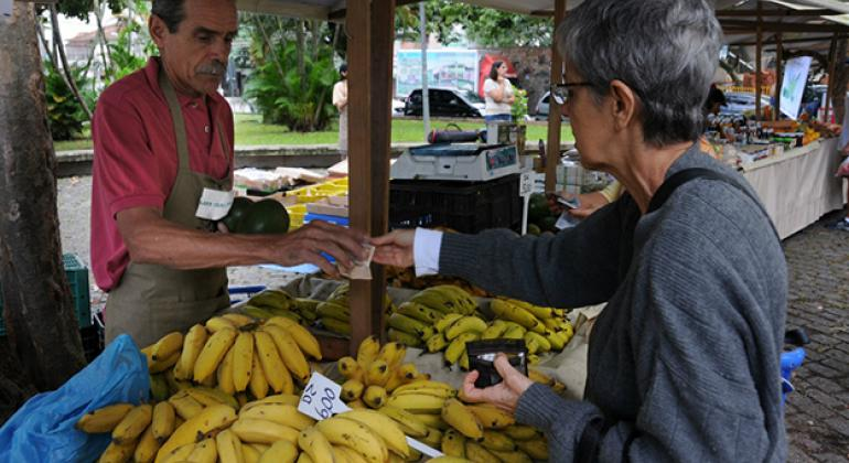 A banana vendor making a sale at the São José Slow Food Market. The UN Food and Agriculture Organization (FAO) is working to protect banana crops from the Fusarium Wilt TR4 disease.