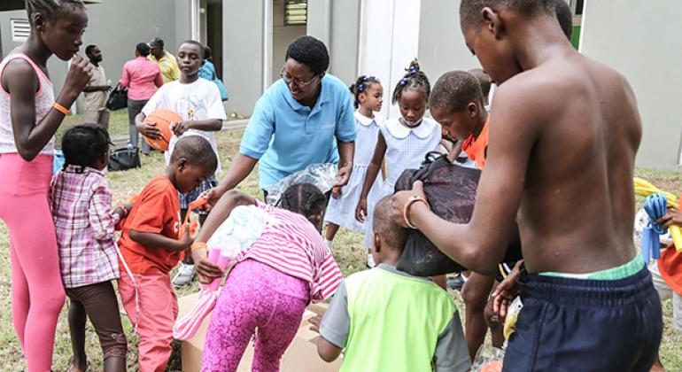 Muriel Mafico (in blue top) distributing UNICEF educational and recreational supplies to children at a shelter for hurricane evacuees in Antigua. © UNICEF/UN0121369/Moreno Gonzalez