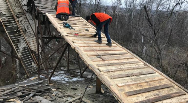 Reconstruction of a wooden footbridge in Stanytsia Luhanska in eastern Ukraine, one of only a handful of places where people can cross the front line.