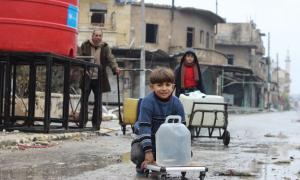 In east Aleppo City, Syria, boys and a man collect water from a UNICEF-supported water point in Shakoor neighbourhood.
