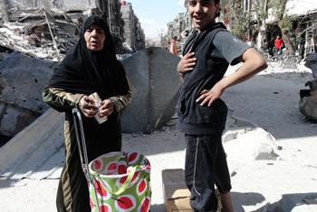 A mother and her son find relief upon receiving an UNRWA food parcel. Yarmouk, Damascus.