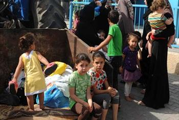 Palestinian families take shelter at an UNRWA school in Gaza City (13 July 2014).