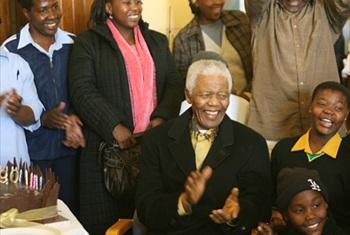 Mr. Mandela, surrounded by children, clapping his hands and 90th birthday cake on the table. NMF Photo/Juda Ngwenya