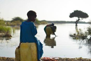 A young girl sits on a jerry can, as her mother fills up another with water, near the town of Jowhar, Somalia.