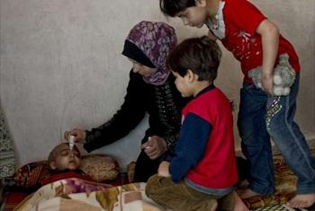 Four-year-old Syrian refugee Zacharia lies dying of a brain tumour as his mother gives him water and his siblings look on with love and concern. © UNHCR/L.Addario