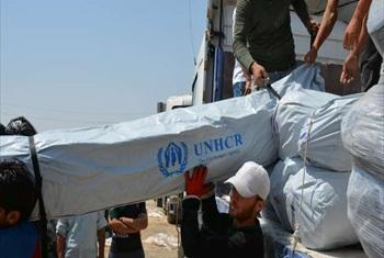 Workers unload trucks laden with hundreds of tents for families displaced by recent fighting in Iraq .© UNHCR/E.Colt