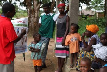 A team of volunteers in Gbaneh Bana Village, Port Loko District, Sierra Leone, discussing Ebola prevention with a family.