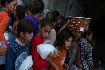 A group of internally displaced Iraqi girls queue for food at a community kitchen in a village in Iraqi Kurdistan's Dohuk governorate.© UNHCR/B.Szandelszky