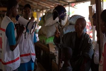 UNICEF and partners visit a crowded market in Conakry, Guinea, to explain to vendors how they can protect themselves and their families from Ebola.