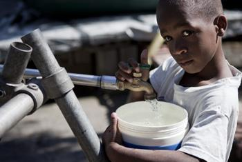 A child collects water in Haiti.