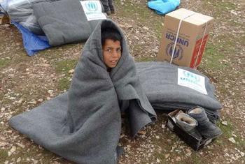 A young Syrian refugee wraps himself up in a thick blanket, part of aid to help his family weather the winter in northern Iraq.