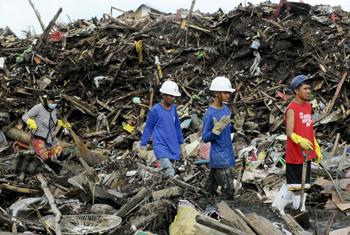 A group of clean-up workers in Tacloban walk through piles of debris left by the storm. (file photo/2013)