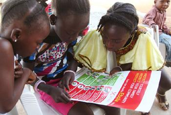 Girls in the city of Voinjama look at a poster that displays information and illustrations about how to prevent the spread of Ebola.