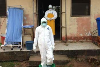 Denis dons protective gear to go see his wife inside the confirmed case ward. (c) Nigeria/2014/Denis - UNICEF