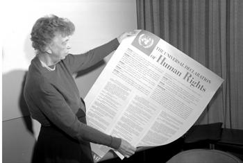 Mrs. Eleanor Roosevelt holding a Declaration of Human Rights poster in English.