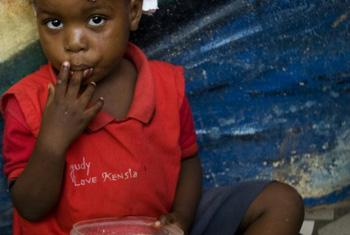 A Haitian child eats food distributed by the UN peacekeepers at the Amanda Marga Special Academic Institute.