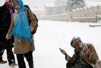 A poor man asks passersby for money on a snowy day in Afghanistan.