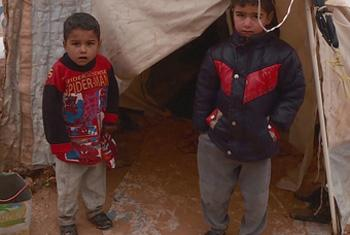 Syrian refugee children standing in front of a collapsed tent. (UNifeed video capture)