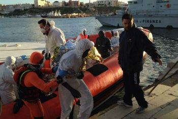 Italian coastguards arrive at the quay in Lampedusa with survivors of this week's tragedy in the Mediterranean.