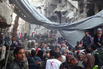 Crowd awaits relief aid at Yarmouk Palestinian refugee camp in Damascus.